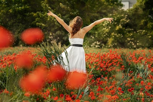 髪を飛んでケシ畑で美しい若い女性