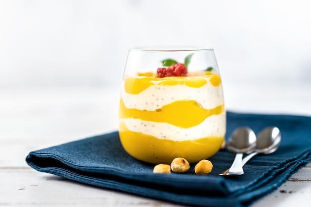 Крупным планом манго пюре с йогуртом на белом столе