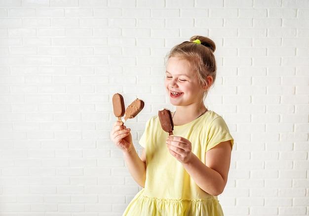 夏の時間でアイスクリームアイスキャンデーを食べることの幸せな女の子