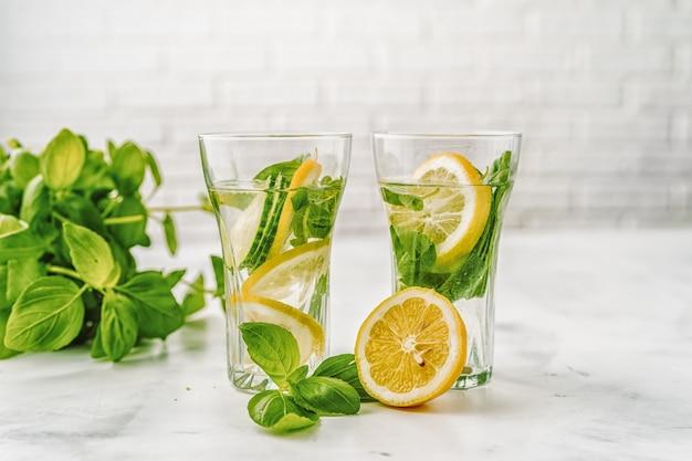 デトックスキュウリとレモンの白い背景の上の水を注入