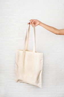Женская рука держит эко сумку на белом фоне