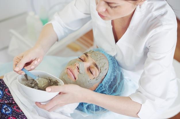 藻類のマスクを適用する美容師。