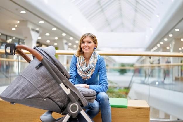 ショッピングセンターで赤ちゃんを持つ若い女