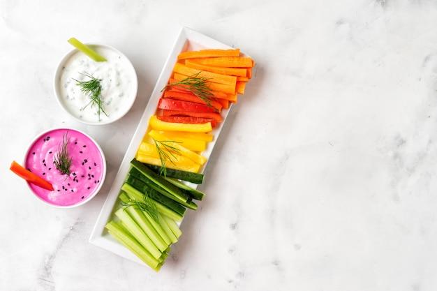 Красочные овощные палочки с соусом из йогурта. вид сверху.