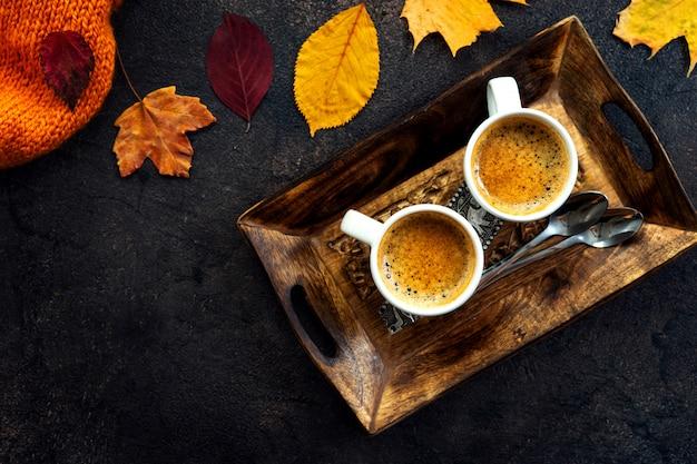 黄色の葉の周りのコーヒーカップのトップビュー