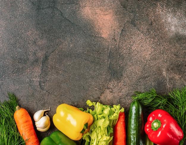 新鮮な野菜の境界線を持つ暗い素朴な背景。上面図。