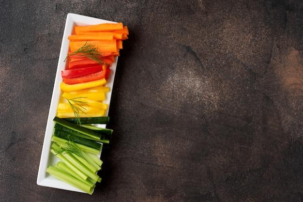 Красочные овощные палочки в длинной тарелке. вид сверху.