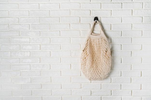 ホワイトウォールに掛かっている白い綿ネットバッグ