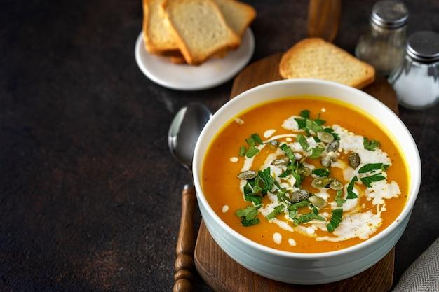 Тыквенный суп со сливками и петрушкой на темном деревенском столе