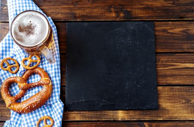 ビールジョッキ、プレッツェル、木製のテーブルのソーセージ。上面図