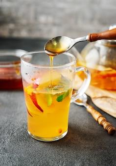 アップルティーのガラスカップに蜂蜜を注ぐ