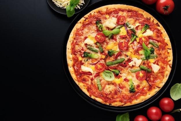 チーズ、オリーブ、バジル、新鮮な野菜と食欲をそそるベジタリアンピザのトップビュー
