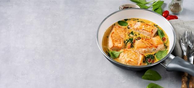 Стейки лосося на сковороде с кремом на свету
