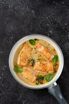 Крупным планом стейки лосося в сливочном соусе на черном