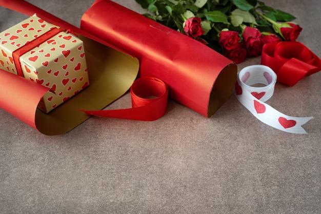 Подарочная коробка, завернутая в красную бумагу, розы и упаковочные материалы на коричневом