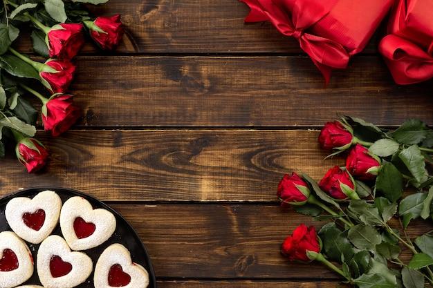 Красные розы, подарочные коробки, печенье из линзы на темном деревянном