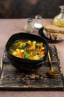 Весенний овощной суп в черной миске
