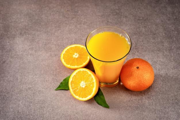 Стакан свежего апельсинового сока и апельсины
