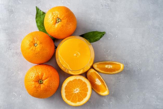 Вид сверху свежего апельсинового сока, апельсинов и ломтиков