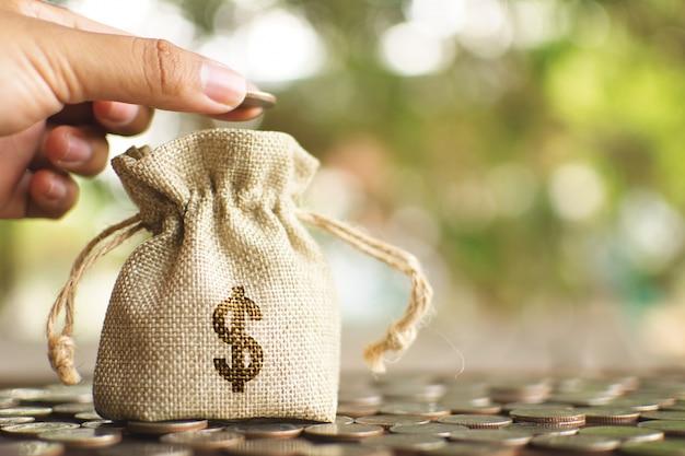 女性の手が袋にお金を落とします。