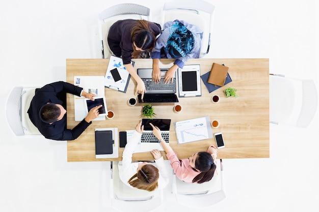 ビジネスチームの同僚は現代の事務室で彼のラップトップ電話に取り組んで仕事