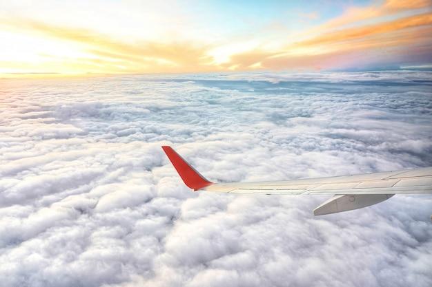 雲と日の出の空の上を飛んでいる飛行機の翼