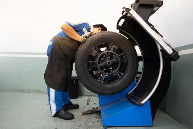 Человек механика работая и ремонтируя или проверяя автошины с машиной колеса в магазине автошин.