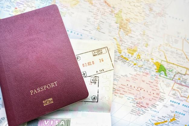 世界の地図上のパスポート。ビザで出発と到着のスタンプ。旅行の旅休暇の概念。