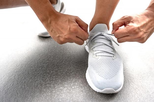 練習前にランニングシューズに靴ひもを結ぶ男性の手。トレーニングの準備をしているランナー。スポーツ選手のアクティブなライフスタイル。