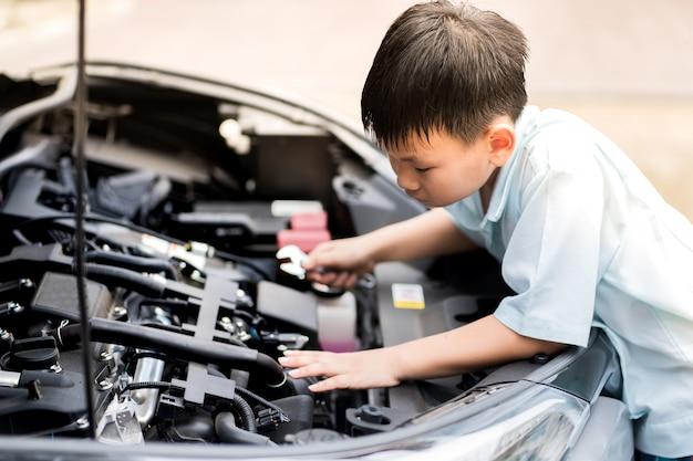 メカニックの少年が働いて、車サービスセンターで車のエンジンを修復します。自動車の金属自動車エンジン部品の詳細。