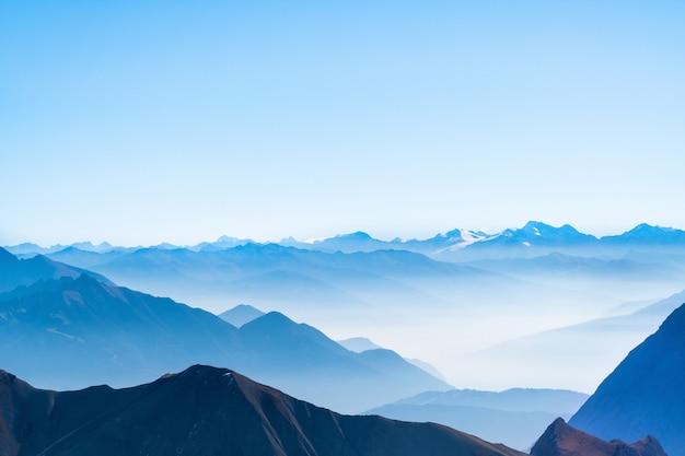 ドイツアルプスツークシュピッツェでレイヤー山、青い空と雲の背景の風光明媚なパノラマ写真またははがきビュー