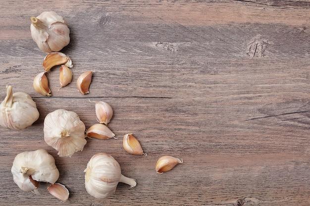 Гвоздичные дерев чеснока на деревянной предпосылке таблицы стола винтажной на кухне.