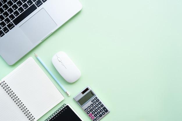 Рабочая область с калькулятором, ручкой, ноутбуком, обратите внимание на пастельных зеленом фоне.