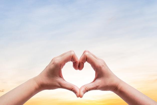 Женщина держит руки до неба в форме сердца любви на солнечной вспышки света и облака с ясного неба