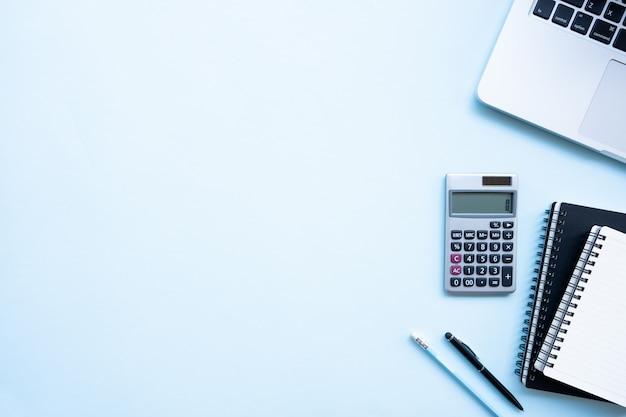 Вид сверху офисный стол письменный стол. рабочая область с калькулятором, черная ручка, ноутбук синий