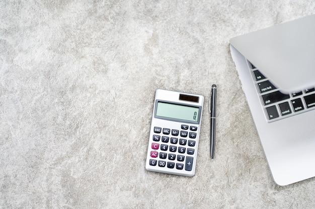 Рабочая область с калькулятором, ручкой, ноутбуком на сером бетоне
