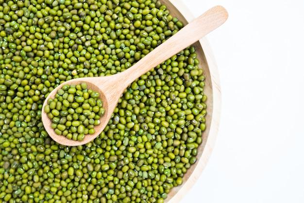 Сырые свежие семена бобов мунг или органические зеленые бобы в деревянной миске и деревянной ложкой на столе деревянные пластины.