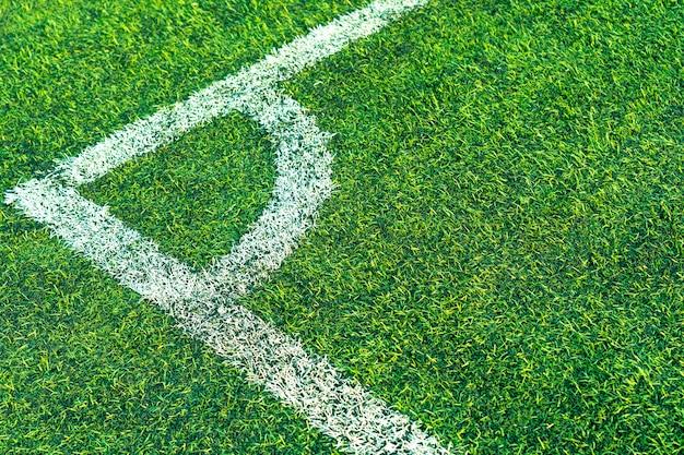 スタジアムで人工芝。白い縞模様のラインと抽象的なフットボールの芝生グラウンド背景。