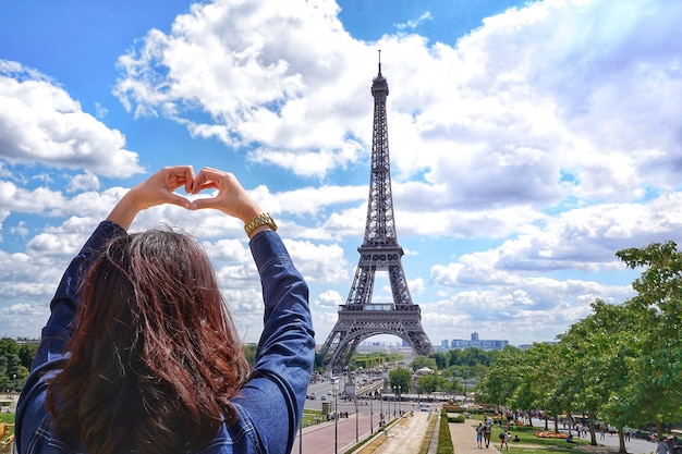 Девушка в руке сердце знак с джинсовой рубашке в летние каникулы на небе и эйфелева башня в фоновом режиме в париже