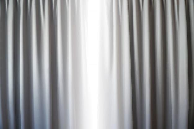 ウィンドウの背景に日光のあるリビングルームのカーテンの室内装飾