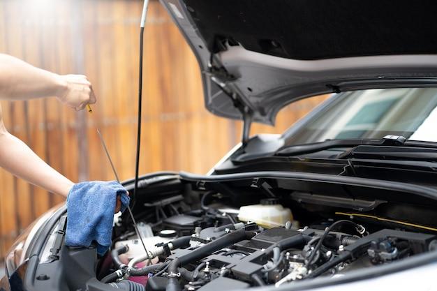 Человек механика работая и ремонтируя или проверяя двигатель масла автомобиля.