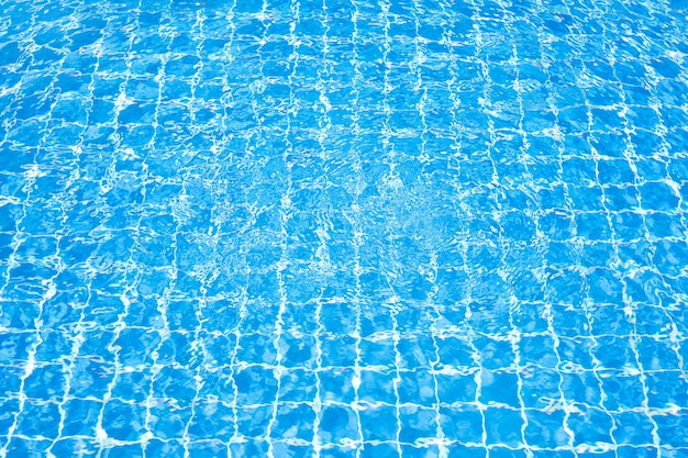 太陽の反射とスイミングプールの青い水の表面。プール内の波