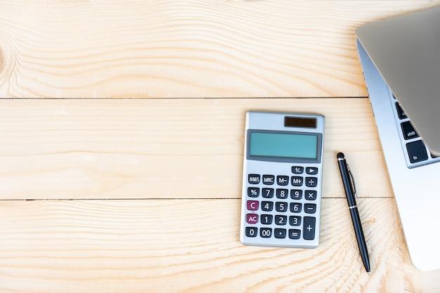 電卓、黒ペン、松の木の背景にラップトップを持つワークスペース。