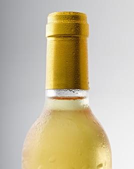Капля воды на бутылке белого вина