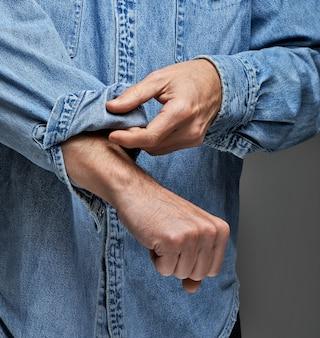 Человек в джинсовой рубашке закатывает рукава