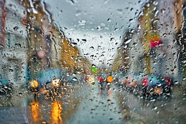 雨と嵐の抽象的な背景で運転する車