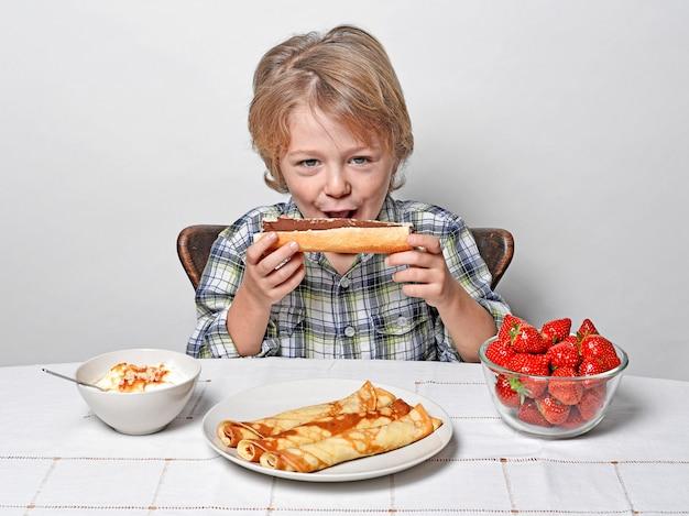 Мальчик ест французский хлеб с шоколадом