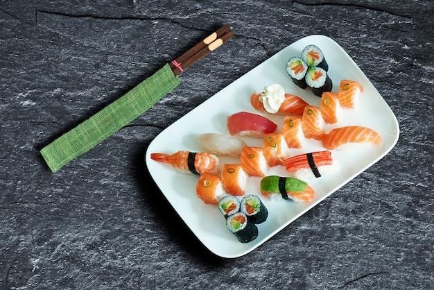 Тарелка вкусных суши и маки на фоне текстуры