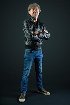 Портрет мужчины с кожаной курткой и джинсовыми брюками