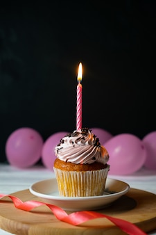 ピンクの風船と黒のキャンドルでハッピーブリスデーケーキ
